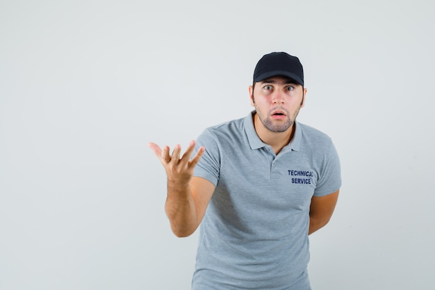 Jeune technicien qui tend la main dans un geste perplexe en vue de face uniforme gris.
