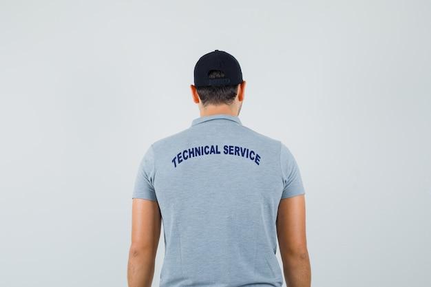 Jeune technicien regardant ailleurs en uniforme gris et à la vue de dos, focalisé.