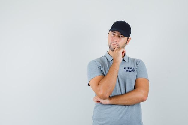 Jeune technicien soutenant le menton sur place en uniforme gris et l'air hésitant.