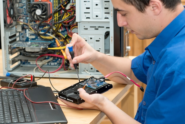 Jeune technicien travaillant sur un ordinateur cassé dans son bureau
