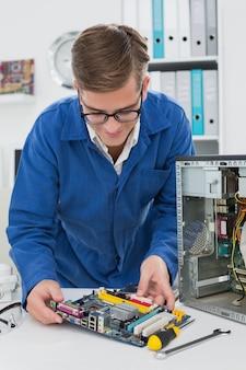 Jeune technicien travaillant sur un processeur cassé