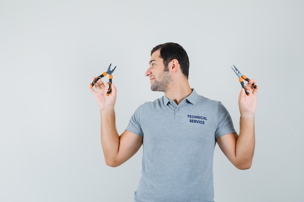 Jeune technicien en uniforme gris regardant la pince tenant à deux mains et à l'optimiste, vue de face.