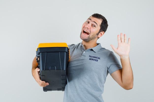 Jeune technicien en uniforme gris tenant la boîte à outils tout en saluant quelqu'un et à l'optimiste.