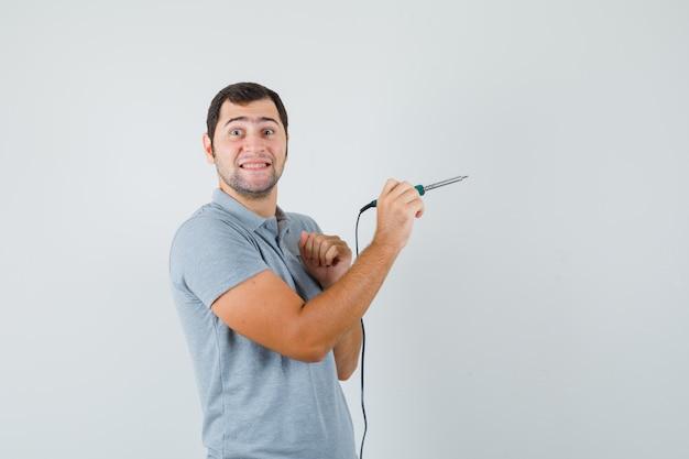 Jeune technicien en uniforme gris tenant la perceuse dans une main tout en montrant le pouce vers le haut et à la bonne humeur.