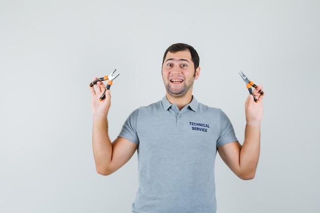 Jeune technicien en uniforme gris tenant une pince à deux mains et à l'optimiste, vue de face.