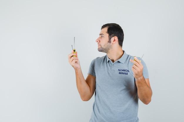 Jeune technicien en uniforme gris tenant des tournevis à deux mains et à la recherche concentrée.
