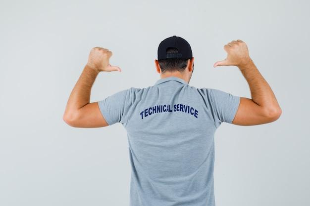 Jeune technicien en uniforme montrant son t-shirt et l'air fier, vue arrière.