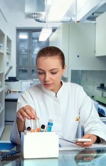 Jeune technicienne ou scientifique sélectionne un tube échantillon dans une glacière