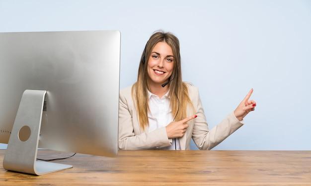 Jeune télévendeur femme pointant le doigt sur le côté