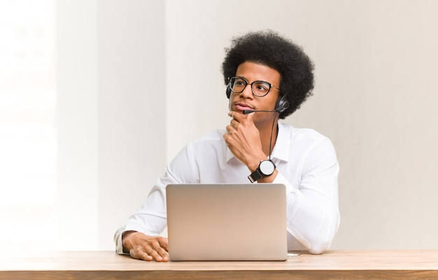 Jeune télévendeur homme noir doutant et confus