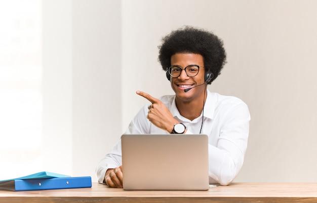 Jeune télévendeur homme noir souriant et pointant vers le côté