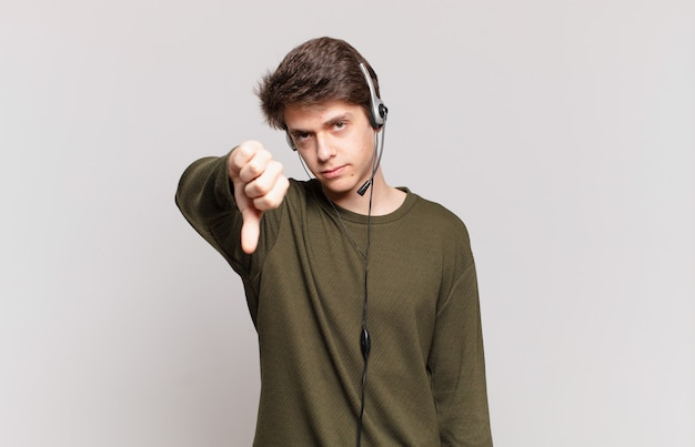 Jeune télévendeur se sentant fâché, en colère, agacé, déçu ou mécontent, montrant les pouces vers le bas avec un regard sérieux