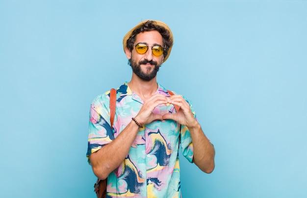 Jeune touriste barbu souriant et se sentant heureux, mignon, romantique et amoureux, en forme de coeur à deux mains