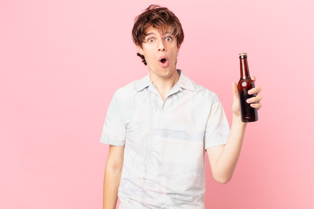 Jeune touriste avec une bière à la recherche de très choqué ou surpris