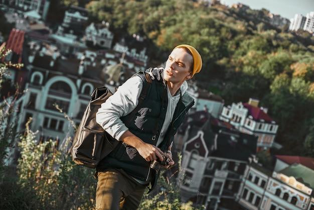 Un jeune touriste blogueur élégant prend des photos de bâtiments rétro