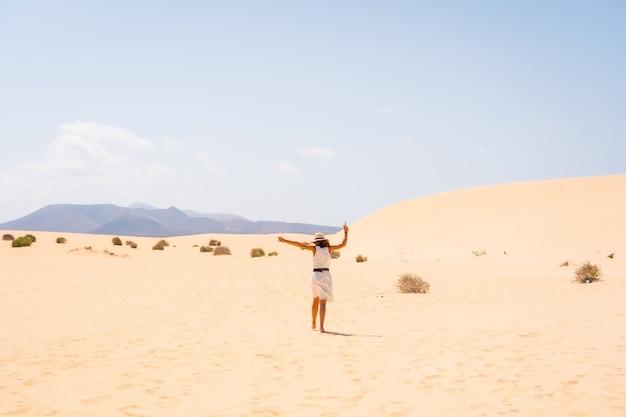 Un jeune touriste caucasien vêtu d'une robe blanche et d'un chapeau marchant dans les dunes du parc naturel de corralejo, fuerteventura, îles canaries. espagne