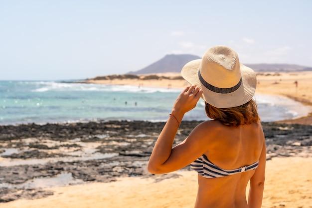 Un jeune touriste avec un chapeau sur les plages du parc naturel de corralejo, fuerteventura, îles canaries. espagne