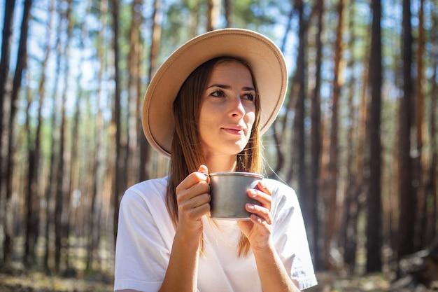 Jeune touriste en chapeau et t-shirt boit du thé ou de l'eau lors d'une halte dans la forêt.