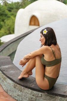 Jeune touriste détendue avec une fleur dans ses cheveux assise près d'une piscine extérieure