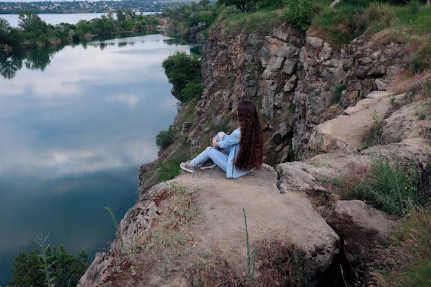Une jeune touriste est assise sur le dessus du support et regarde un beau paysage. randonnée femme relaxante au sommet de la falaise en profitant. jolie fille dans des vêtements en jean