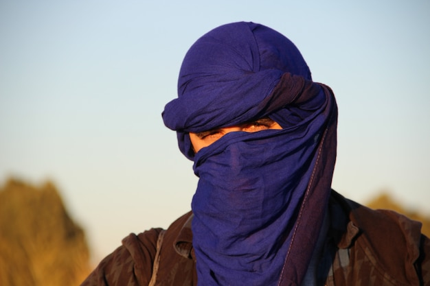 Un jeune touriste européen avec le foulard berbère bleu dans le désert de merzouga