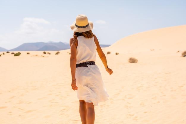 Un jeune touriste européen portant un chapeau marchant à travers les dunes du parc naturel de corralejo, fuerteventura, îles canaries. espagne