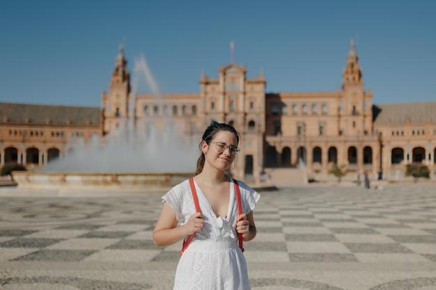 Jeune touriste femme vêtue d'une robe blanche sourit à la caméra en se tenant debout sur la plaza de espana