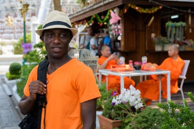 Jeune touriste homme pensant tout en tenant sac à dos contre vue de moines assis au café et temple wat arun à bangkok en thaïlande