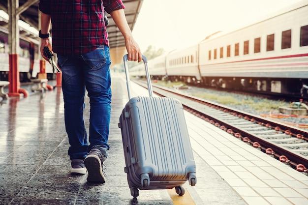 Jeune touriste, marche, glisser, bagage autre main tenant la carte et marcher vers le train
