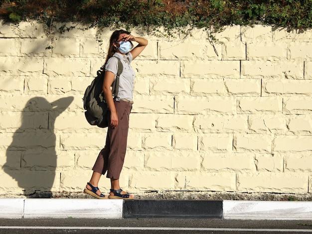 Une jeune touriste en masque facial se tient sur le bord de la route et se couvre les yeux du soleil