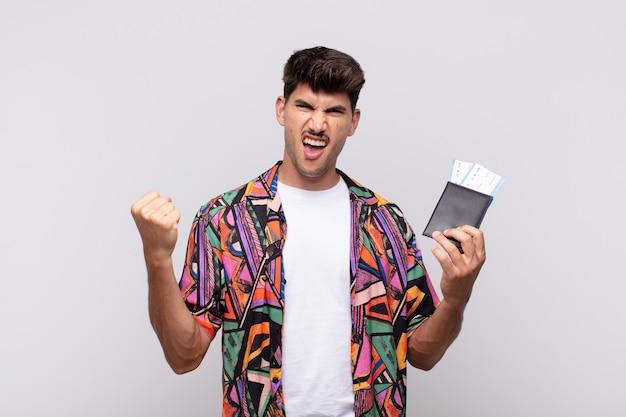 Jeune touriste avec un passeport criant agressivement avec une expression de colère ou avec les poings serrés célébrant le succès