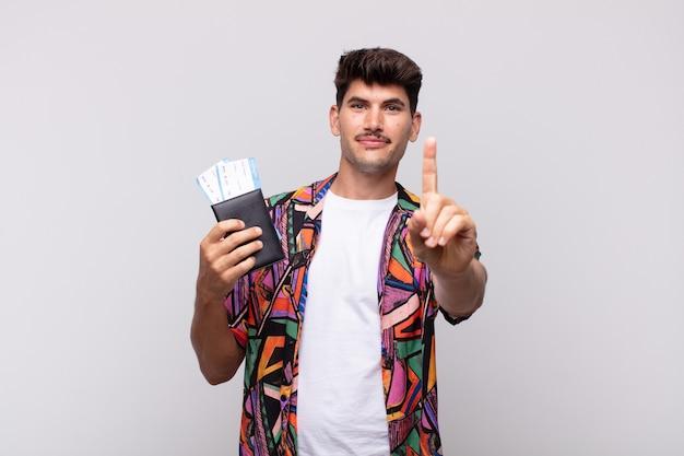 Jeune touriste avec un passeport souriant fièrement et en toute confiance faisant le numéro un poser triomphalement, se sentir comme un chef