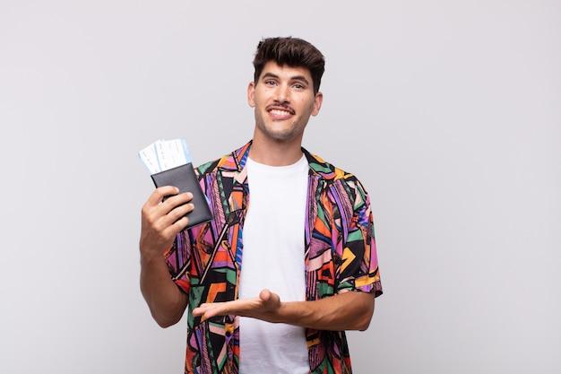 Jeune touriste avec un passeport souriant joyeusement, se sentant heureux et montrant un concept dans l'espace de copie avec la paume de la main