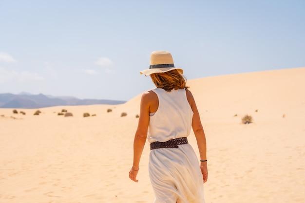 Un jeune touriste portant un chapeau marchant le long du sable sur les plages du parc naturel de corralejo, fuerteventura, îles canaries. espagne