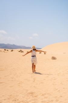 Un jeune touriste portant un chapeau marchant à travers les dunes du parc naturel de corralejo, fuerteventura, îles canaries. espagne
