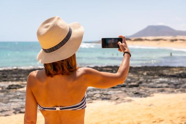 Un jeune touriste prenant une photo sur les plages des dunes du parc naturel de corralejo, fuerteventura, îles canaries. espagne