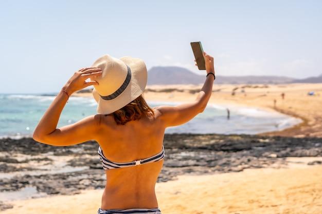 Un jeune touriste prenant une photo avec le téléphone sur les plages du parc naturel de corralejo, fuerteventura, îles canaries. espagne