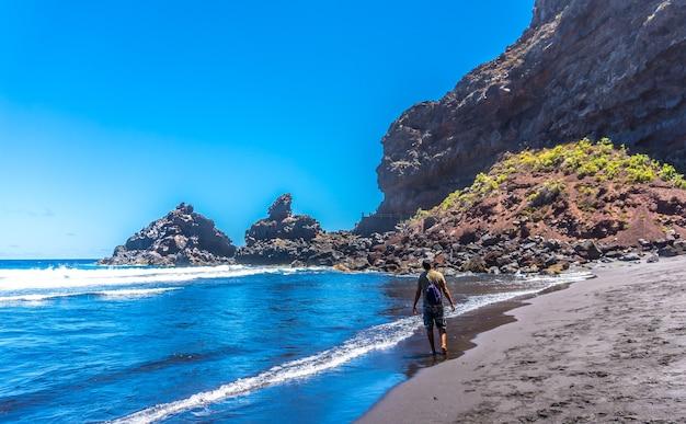 Un jeune touriste profitant de l'été au bord de la mer sur des rochers à playa de nogales à l'est de l'île de la plama, îles canaries. espagne