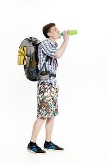 Jeune touriste avec un sac à dos d'eau potable sur fond blanc