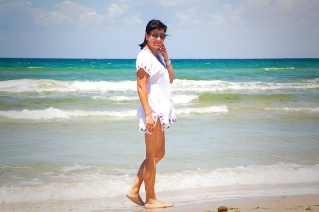Jeune touriste en tunique et lunettes de soleil sur fond de mer méditerranée, plage de sable. fille en vacances. tons chauds du jour. dame marchant sur la plage, ville de vacances à tunis, afrique, au début du printemps
