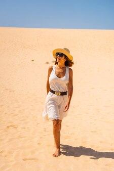 Un jeune touriste vêtu d'une robe blanche et d'un chapeau marchant dans les dunes du parc naturel de corralejo, fuerteventura, îles canaries. espagne