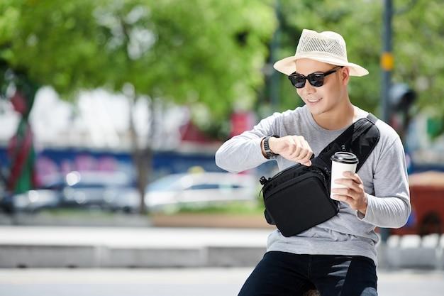 Jeune touriste vietnamien positif en chapeau de soleil et lunettes de soleil assis contre la route de la ville et vérifiant l'heure en buvant du café en été