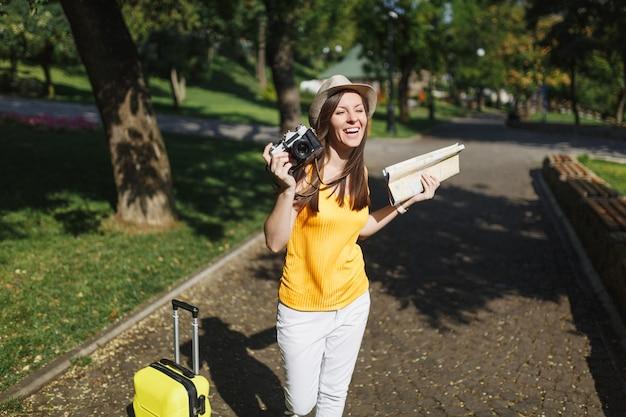 Jeune touriste voyageur riant femme au chapeau avec valise, plan de la ville tenant un appareil photo vintage rétro dans la ville en plein air. fille voyageant à l'étranger pour voyager le week-end. mode de vie de voyage touristique.