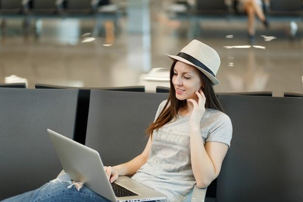 Jeune touriste voyageur songeur femme assise travaillant sur un ordinateur portable pensant attendre dans le hall de l'aéroport international