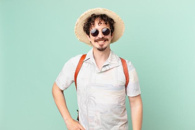 Jeune touriste voyageur souriant joyeusement avec une main sur la hanche et confiant