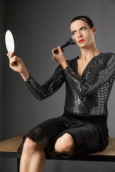 Jeune transgenre à l'aide d'un pinceau à maquillage