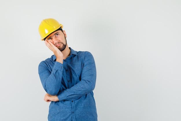 Jeune travailleur appuyé sur la joue sur la paume surélevée en chemise, casque et à la réflexion.