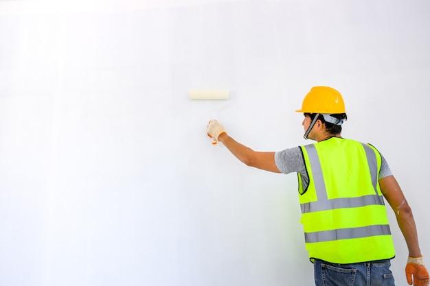 Jeune travailleur asiatique en tant que peintre pour peindre les murs de la maison et utiliser un rouleau pour peindre l'apprêt blanc sur le chantier de construction