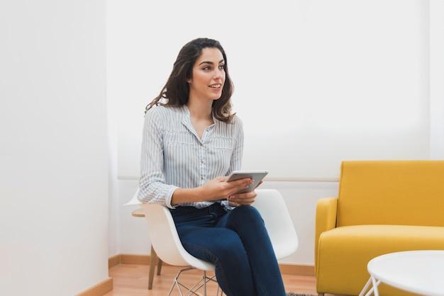 Jeune travailleur assis sur une chaise et parler à quelqu'un