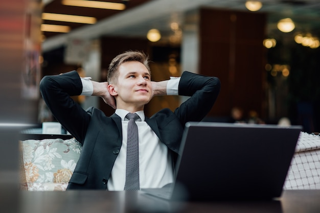 Jeune travailleur ayant une pause et se reposer après avoir résolu la tâche, vêtu d'un costume noir au centre commercial